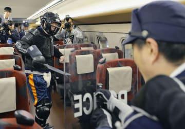 北陸新幹線の車内で行われた無差別殺傷事件を想定した訓練で、刃物を手にする男(左)と向き合う警察官=19日午前、石川県白山市