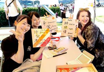 外国人観光客(右)に色紙をプレゼントする宇和島東高生(宇和島商工会議所提供)