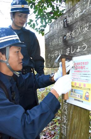 登山道に遭難防止の注意点を呼び掛けるパネルを設置する大津署員(大津市田上里町)