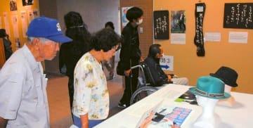 翁長雄志さんの言葉や遺品に見入る来場者=沖縄市役所1階・市民ギャラリー
