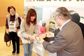 植田館長(右)から記念品を受け取る宇山敦子さん