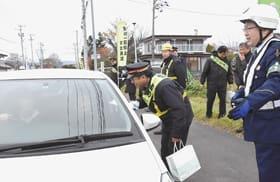 啓発物をドライバーに手渡し、踏切での事故防止を呼び掛ける参加者