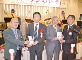 市教委の佐藤部長(左から2人目)と社協の山田会長(同3人目)に善意を手渡した田中会長(左)と勝俣会長