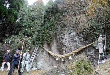 23日の例大祭を前に「的石」に長さ約8メートルの大しめ縄を飾り付ける住民ら=阿蘇市