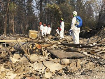 山火事で燃えた家の跡地で捜索活動をする人たち=18日、米カリフォルニア州パラダイス(AP=共同)