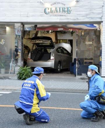 美容院に突っ込んだ乗用車(奥)=20日午後、神奈川県横須賀市