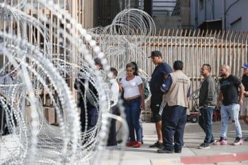 国境検問所で旅券などのチェックを受ける人たち。有刺鉄線を張り巡らしたバリケードが設置されていた=19日、メキシコ北西部ティフアナ(共同)