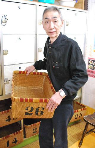柳行李を持つ前田さん。廃業した銭湯からもらい受けたものもあるそう(大津市中央3丁目・神楽湯)