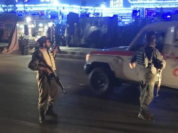 20日、アフガニスタン・カブールの爆発現場を警備する警察官(ロイター=共同)