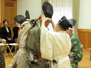 【烏帽子をかぶせてもらう学生=伊勢市神田久志本町の皇學館大学で】