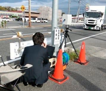 【可搬式ナンバー読取装置を使って車検切れを検査する職員=亀山市関町で(中部運輸局三重運輸支局提供)】