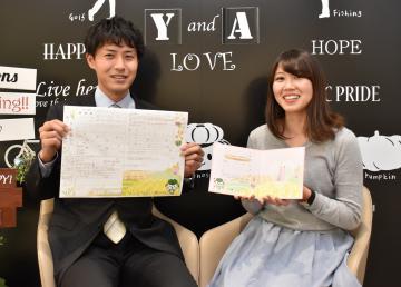 記念撮影用ボードの前で、オリジナル婚姻届(左)と結婚記念証を手にする稲敷市職員=2日、市役所