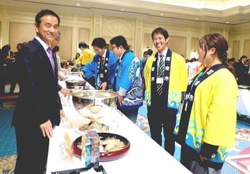 山口県が誇る「食」が披露され、盛り上がった交流会。村岡知事(左)もスタッフを激励=19日、大阪市内のホテル