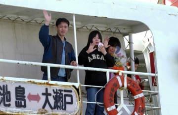 デッキに並び、見送りの人に手を振る深江さん一家=長崎県西彼外海町池島、池島港