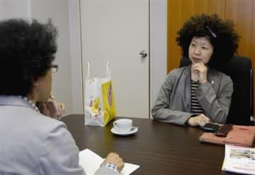 アフロヘアがトレードマークの稲垣えみ子さん(右)と、取材する中原功一朗記者=熊本市中央区