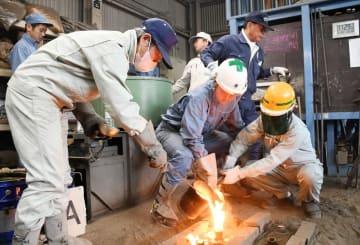 鉄を鋳型に流し込む生徒=佐賀市の佐賀工業校