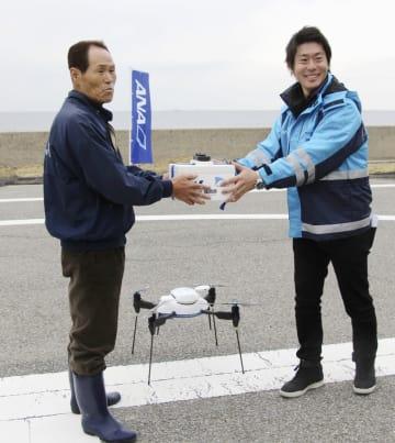 ANAホールディングスの担当者(右)から小型無人機ドローンで運ばれた荷物を受け取る玄界島の住民=21日午後、福岡市西区