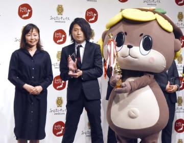 大賞に選ばれ表彰される高知県須崎市の守時健さん(中央)と市のキャラクター「しんじょう君」=21日午後、東京都港区