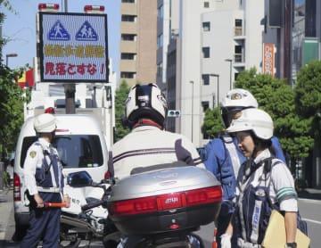 5月、歩行者が横断中の横断歩道で、一時停止を怠ったドライバーらに指導する警察官=東京都内