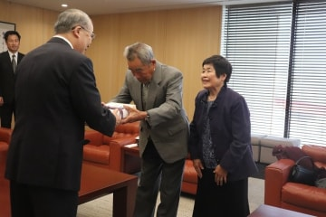 中村知事に宮中献穀米を手渡す川谷光男さん(中央)と芳恵さん(右)=長崎県庁