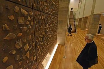 一般公開が始まった縄文時遊館の展示収蔵施設。高さ約6メートルの縄文ビッグウォールでは、来場者がちりばめられた土器片に見入っていた=22日午前