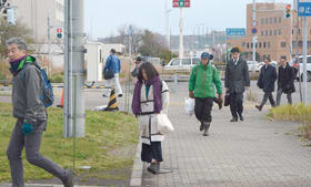 コートやマフラーなどの防寒着を着用し、足早に職場に向かう市民=22日午前8時10分ごろ、室蘭市海岸町