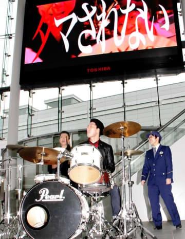 大型ビジョンに流れるMVに合わせ、ドラムを演奏する久保顕理さんら=11月19日、福井県福井市のハピテラス