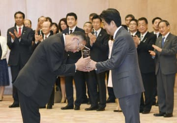 「ディスカバー農山漁村の宝」のグランプリに選ばれ、安倍首相(右)から表彰を受ける栃木県茂木町の「もてぎプラザ」の関係者=22日午後、首相官邸