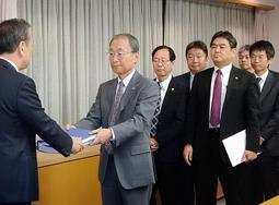 神戸市の岡口憲義副市長(左)に中間報告を手渡す第三者委員会の工藤涼二委員長ら=神戸市役所