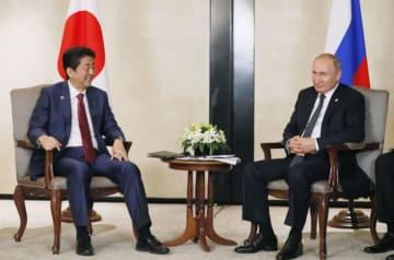 会談する安倍首相(左)とプーチン大統領=14日、シンガポール(共同)