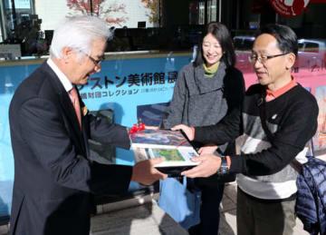 池田館長(左)から3万人目の記念品を受け取る池永さん夫妻