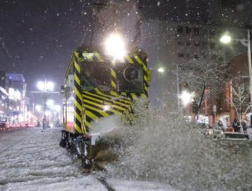 今シーズン初めて出動し、線路に積もった雪を掃き飛ばす「ササラ電車」=22日夜、札幌市中央区