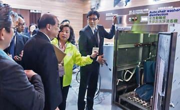 車いすを自動洗浄・消毒する設備について、関係者から説明を受ける張政務長官(左2)=22日、HKCEC(香港政府提供)