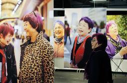 髪を紫に染めた女性の写真が並ぶ会場=KIITO