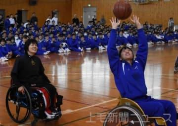 塚本さん(左)の指導を受けてシュートに挑戦する生徒