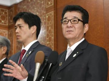 22日、記者団の質問に答える松井一郎大阪府知事。左は吉村洋文大阪市長=パリ(共同)
