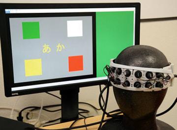 安村明准教授らが開発した検査装置。脳の血流を調べるバンドを頭に巻いて、パネルの文字が指示する色に触れてもらう仕組み=熊本大