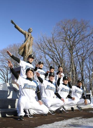クラーク博士像前でポーズをとる吉田輝星投手(前列左から2人目)ら日本ハムの新入団選手=23日、札幌市