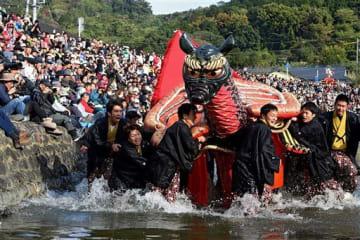 多くの見物客が見守る中、砥崎河原で水しぶきを上げながら演舞を披露する亀蛇=23日、八代市(上杉勇太)