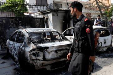 23日、パキスタン南部カラチの中国総領事館襲撃後、大破した車両のそばを歩く兵士(ロイター=共同)