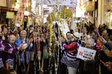 2025年万博の大阪開催が決まり、くす玉を割って祝う人たち=24日未明、大阪・道頓堀