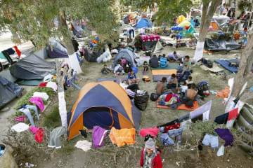 メキシコ北西部ティフアナの収容施設で、テントなどで生活する移民ら=19日