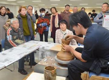 ろくろで粘土を成形する様子に見入る来場者=23日、鳥取市富安2丁目の日本海新聞ビル5階ホール