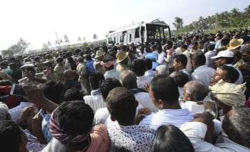 24日、インド南部カルナタカ州で水路に転落後、引き上げられたバス(奥)と集まった人たち(AP=共同)