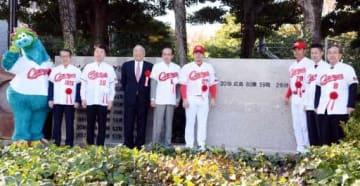 新たな記念碑の前で記念撮影する緒方監督(右から3人目)たち