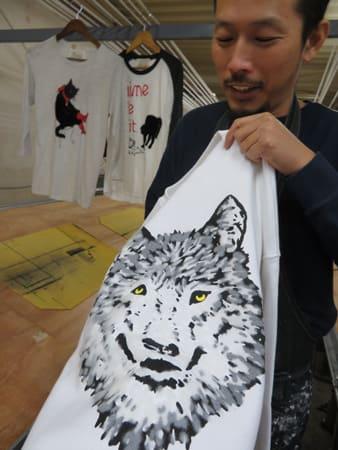 細い繊維を植え付けて立体的なデザインに仕上げたトレーナーを持つ吉田さん。自社ブランドを立ち上げ、販路を切り開いた(京都市西京区・ティーヘッド)