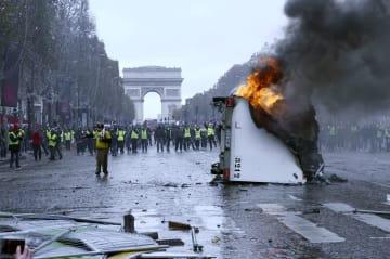 24日、デモ隊と治安部隊が衝突したパリのシャンゼリゼ大通りで炎を上げる車両(共同)