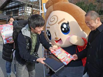 道行く観光客にモバイルスタンプラリーの楽しみ方を説明する岐阜経済大の学生=白川村荻町