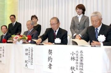 合併契約書に調印する上越市漁協と名立漁協の関係者=24日、上越市