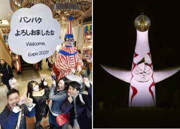 2025年万博の大阪開催を祝う吹き出しが設置された「くいだおれ太郎」と記念撮影する観光客=2028年11月24日午後、大阪・道頓堀  2025年大阪万博の開催決定を祝い、特別にライトアップされた「太陽の塔」=11月24日未明、大阪府吹田市